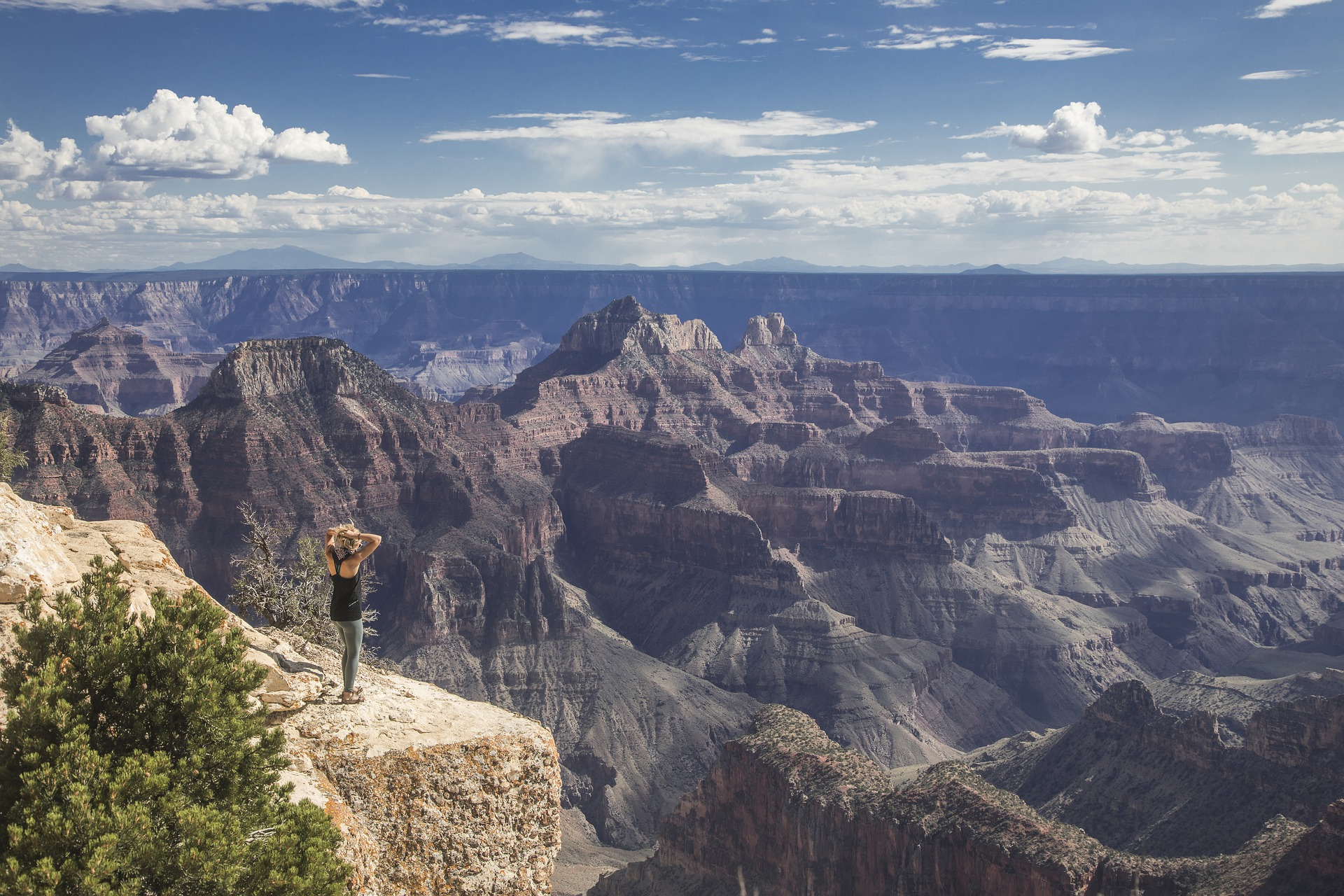 Woman standing on a cliff at the Grand Canyon.