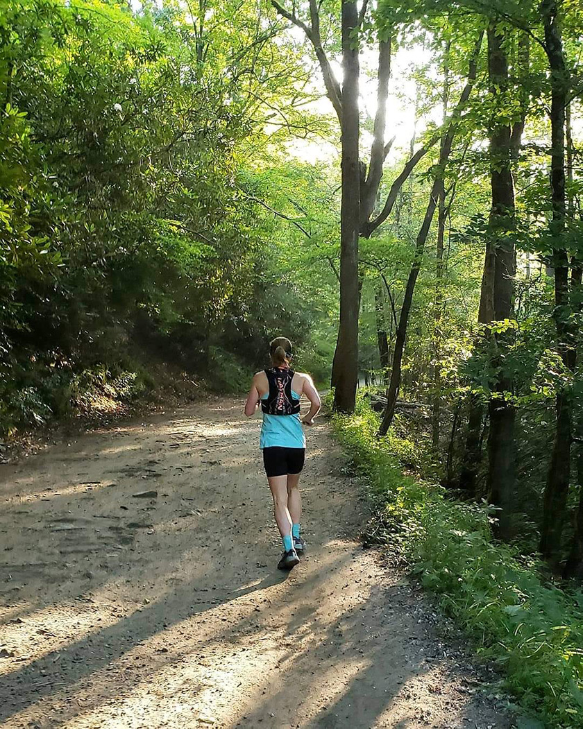 A woman training by running on a trail.